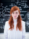 Student in laboratory close up of an attractive a chemistry lab looking the camera with a blackboard on the background Royalty Free Stock Image