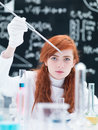 Student laboratory experiment close up of a girl conducting a on a lab table with colorful liquids and lab tools with a blackboard Royalty Free Stock Photography