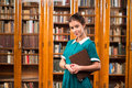 Student lady in library portrait of beautiful girl holding a book and smiling for the camera young getting education Royalty Free Stock Photography