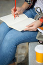 Student lady writing in an open notebook with a pencil Royalty Free Stock Photo