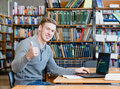 Student with laptop showing thumbs up in the university library Royalty Free Stock Photo