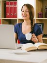 Student laughing in front of laptop photo a beautiful woman using a and drinking coffee at home or at her office Stock Image