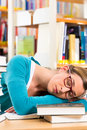 Student in library asleep over books young woman with learning she is tired and overworked Stock Images