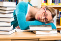 Student in library asleep over books young woman with learning she is tired and overworked Royalty Free Stock Photography
