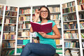 Student in library cheerful young woman holding book and adjusting her glasses while sitting Royalty Free Stock Photo