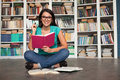 Student in library cheerful young woman holding book and looking at camera while sitting on the floor Royalty Free Stock Images