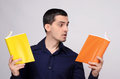 Student looking amazed at the books surprised teacher man in dark blue shirt holding two with orange and yellow blank covers Stock Photography