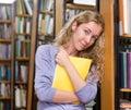 Student mit buch in der bibliothek Lizenzfreies Stockfoto
