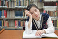Student with open textbook deep in thought young girl front of a library bookshelf looking Royalty Free Stock Image