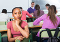 Student outcast in the class portrait of a sad girl sitting lonely while others listening Royalty Free Stock Photos