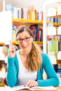Student with pile of books learning in library young woman or girl sitting Stock Image