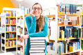 Student with pile of books learning in library young woman or girl sitting Stock Photo