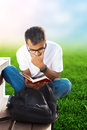 Student reading book a on a beach in the garden Royalty Free Stock Image