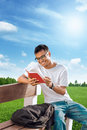 Student reading book a on a beach in the a sunny day Stock Image