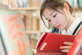 Student reading a book on bookshelf beautiful female red covered in library Stock Images