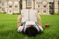 A student reading a book outdoor female college while lying on the park Stock Photography