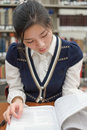 Student reading textbook near bookshelf portrait of young female a in front of library Royalty Free Stock Images