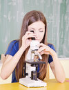 Student in science class using a microscope Stock Images