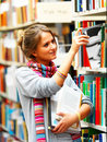 Student selecting book from shelf in a library Royalty Free Stock Photo