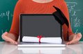 Student showing laptop with mortarboard and degree in classroom Royalty Free Stock Photo