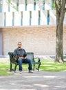 Student sitting on bench på universitetsområdet Royaltyfria Foton