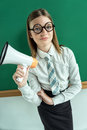 Student standing near blackboard with a megaphone. Royalty Free Stock Photo