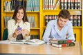 Student studying while friend using mobilephone in young male at table college library Stock Image