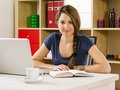 Student studying in front of laptop photo a beautiful smiling woman using a and drinking coffee at home or at her office Stock Photo