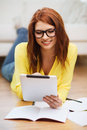 Student with tablet pc computer and notebooks business education technology concept smiling female in eyeglasses at home Royalty Free Stock Photos