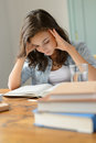 Student teenage girl concentrate reading book home holding her head Stock Images