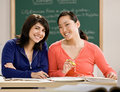 Student with text books doing homework with friend Royalty Free Stock Image