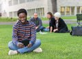 Student using digital tablet on grass at campus male park with friends studying in background Stock Images