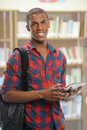 Student using electronic pad young african american in library Stock Photo