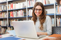 Student using her laptop smiling in a library Stock Photography