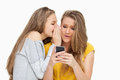 Student whispering to her friend who's texting on her phone Royalty Free Stock Photo