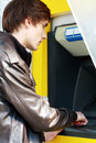 Student withdrawing money young man from an atm cash machine Royalty Free Stock Image