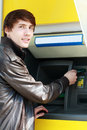 Student withdrawing money young man from a bank cash point outdoors Royalty Free Stock Image