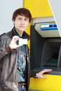 Student withdrawing money young man holding blank credit or business card going to use atm cash machine Stock Photos