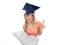 Student woman in mortarboard with encyclopedia people education knowledge and graduation concept smiling young and eyeglasses book Royalty Free Stock Photography