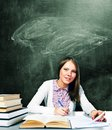 Student woman is sitting at table with chalk board behind her Royalty Free Stock Images