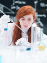 Student working in a chemistry lab close up of girl conducting laboratory experiment on table with colorful liquids and tools with Stock Image