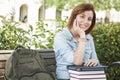 Studentin sitting on campus mit rucksack und büchern Stockbild