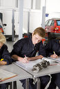 Students with auto part studying automotive trade in vocational school Royalty Free Stock Photo
