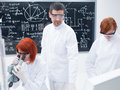 Students in a chemistry lab close up of teacher supervising two during their experiments with blackboard on the background Royalty Free Stock Photography