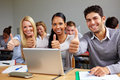 Students in class holding thumbs up Royalty Free Stock Image