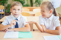 Students or classmates in school classroom sitting together at desk schoolboy thought and girl helps him for the classwork they Royalty Free Stock Photo