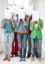 Students covering faces with blank papers education concept group of Royalty Free Stock Image