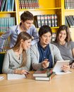 Students with digital tablet discussing in college happy multiethnic library Royalty Free Stock Images