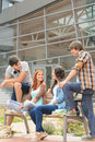 Students friends sitting bench front of university in hanging out Royalty Free Stock Photos