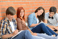 Students friends sitting in row outside college against brick wall writing notes Royalty Free Stock Images